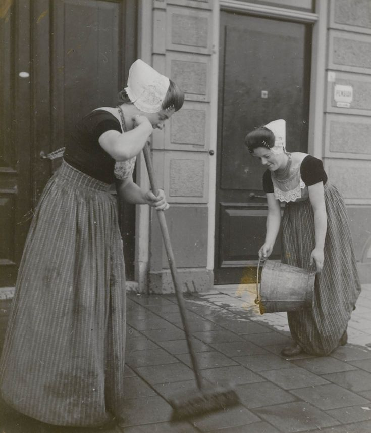 Twee jonge vrouwen in Walcherse streekdracht schrobben de stoep. 1935-1944 #Zeeland #Walcheren