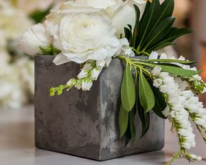 "Square Cement Style Vase. This modern Square Cement Style Vase is a stunning industrial touch to any event or home decor. A sturdy and masculine compliment to any bouquet of blooms. And don't worry, it's not actually heavy cement. It's made of a light weight resin with a true cement like finish, Details:       3 1/2"" (W) x 3 1/2"" (H) Resin"
