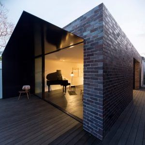 Dark-toned brick extension added to white Federation house in Sydney.