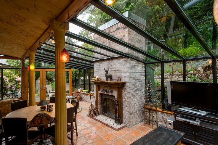The solarium off the kitchen is used as a dining room and den. It has Mexican terra-cotta tile flooring and a wood-burning fireplace.