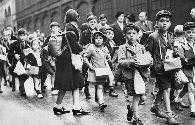 "Child evacuees on their way to the station, Sept 1939. As the evacuees began to settle into their new homes, ""the daily press of that period did much to spread the story of the successful venture. Boys and girls who had never seen farm-life before provided good material for the Press photographer. He was able to snap groups of happy children racing down the village lane when the lunch-bell rang, or setting out on a blackberrying expedition..."""