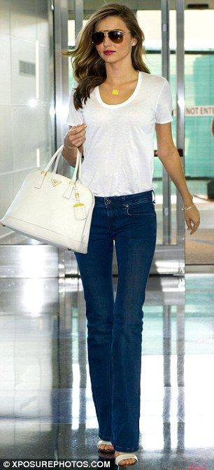 Summer #streetstyle   Miranda Kerr in Isabel Marant white tee, Burberry flared jeans, Gucci sandals and a Prada tote bag