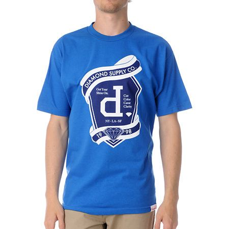 """Rep the Diamond Supply Un Polo Emblem tee shirt for guys. The navy and white custom Diamond Supply Co. graphic at front features a lower case """"d"""" emblem with Diamond Supply Co. 1998 scroll across top and bottom and the company slogan, """"Get your Shine On."""" Printed on a standard fit, royal blue guys crew neck tee shirt with a durable cotton construction. Leave the polo shirts to the lacrosse team and frat boys and throw on the Un Polo Emblem for ridin' in the streets."""