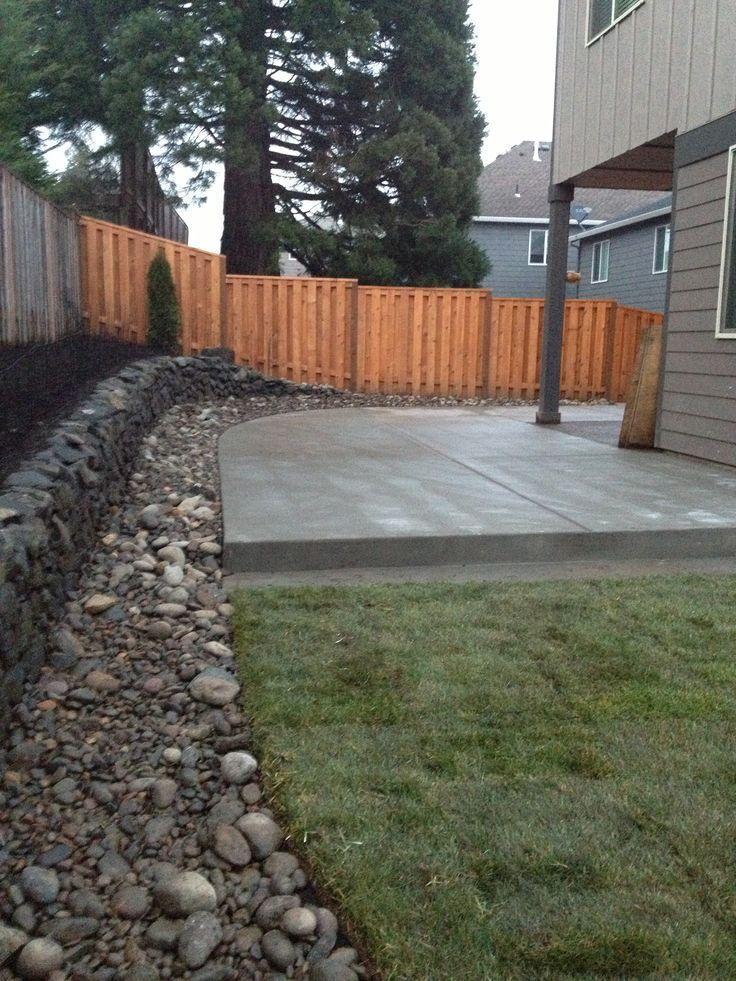 Konkrete Patioflussfelsengrenze Mit Entwasserung Und Rasen Riverrocklandscaping Concrete Backyard Backyard Landscaping River Rock Garden