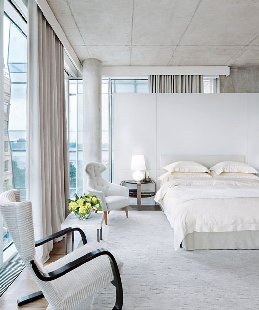 Love the way the industrial cement columns blend with the bedroom's spare but elegant design approach...