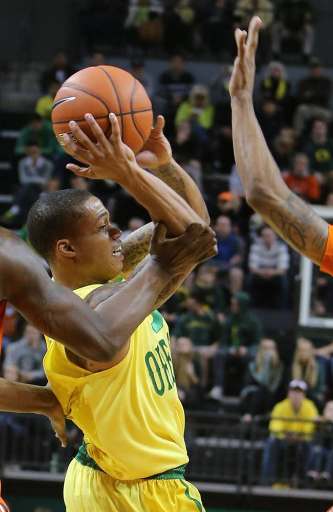Oregon State's Jarmal Reid, left, and Gary Payton II, right, defend Oregon's Joseph Young