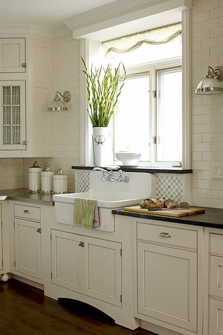 White wall tile, white cabinets + Darker glaze, architectural details (feet under cabinets, floor-arch under sink), tiled-raised backsplash behind sink, black counters