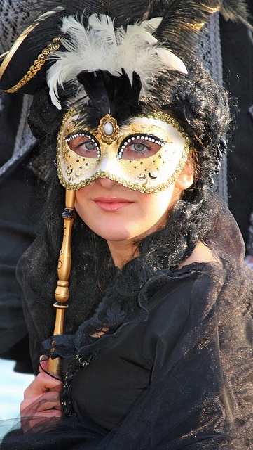 The Columbina is a half-mask, often highly decorated with gold, silver, crystals and feathers. It is held up to the face by a baton or tied with ribbon. Photo by Alaskan Dude.