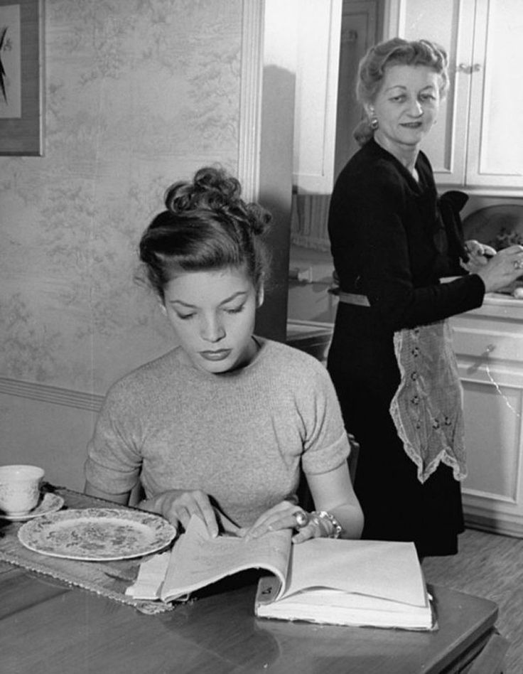 Lauren Bacall studying at home, with her mother behind her.