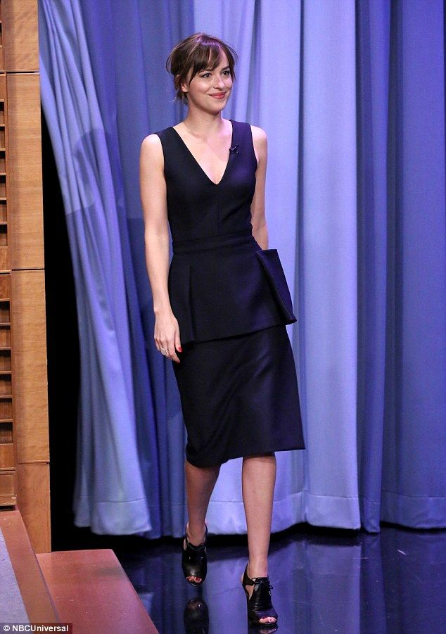 Bursting: Dakota appeared to be stifling a laugh when she strolled on stage in a chic blac...