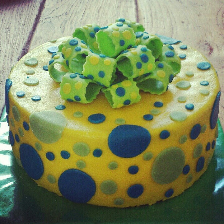 Gele taart met stippen en strik; yellow cake with dots and a fondant bow