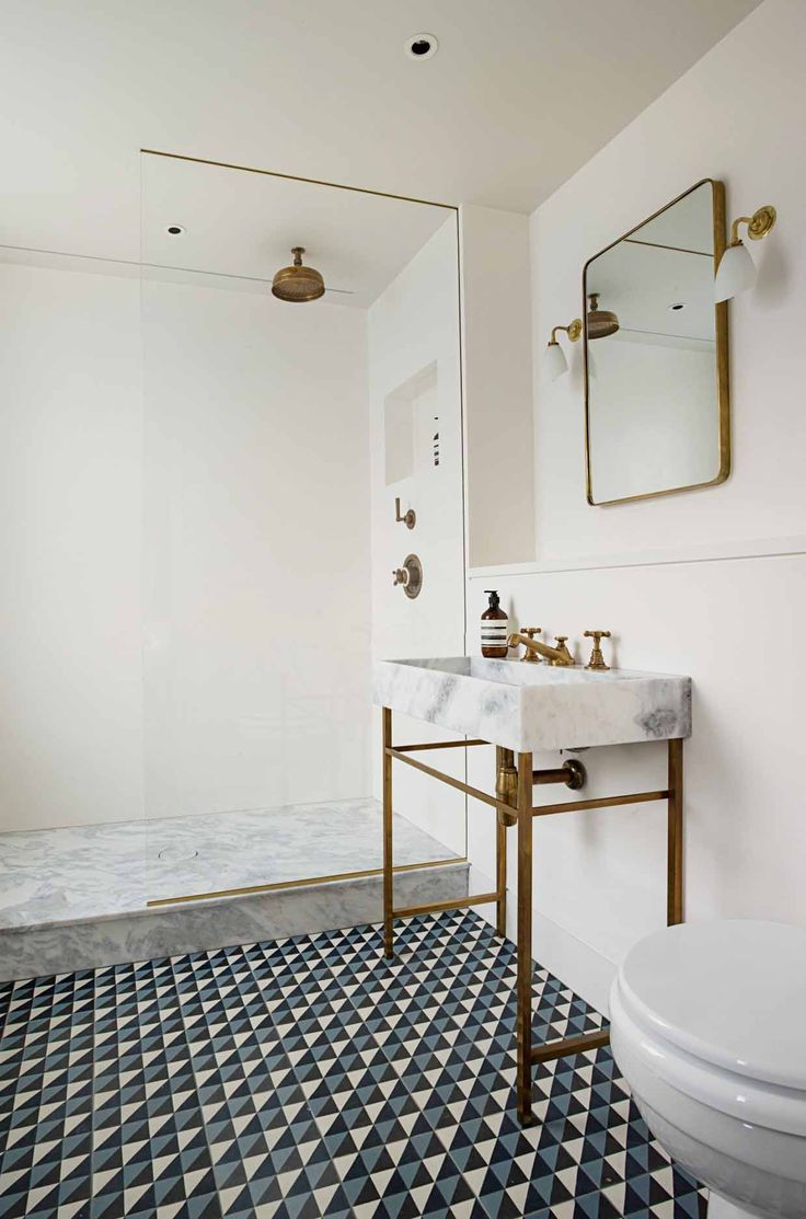 White bathroom with marble sink and brass details