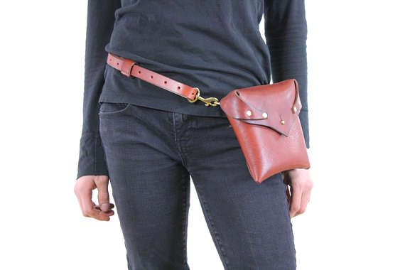 The perfect modern, minimalist, convertible leather fanny pack/purse. Hand made by us from start to finish. Pouch is approximately 6 inches wide, 6 inches tall, and tapers in thickness from about 2 1/4 inches at the top to about 1 inch thick at the bottom. Solid brass button closure with a lid to keep your essentials securely contained. Strap is 3/4 inch wide, and is adjustable for hips 29 and up. Solid brass snaps on either side of strap for easy on/off. Strap can be le...