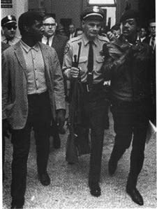 "Bobby Seale (right) at California State Legislature demanding of Capitol guards, ""Am I under arrest?"" No one was arrested inside the Capitol Building."