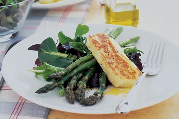 Salty haloumi is pan fried until golden brown and served on a bed of asparagus in this elegant dish.