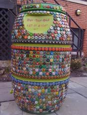 rain barrel decorated with bottle caps! OMG Considering my rainbarrel is a recycled soda syrup barrel... :)
