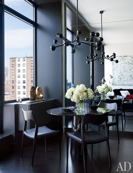 In the dining area, a black-lacquer chandelier hangs above a custom-made marble-top table and vintage J. L. Møller chairs from Belkind Bigi with Spinneybeck leather seats; the bronze sculpture at the window is by Leopoldo Nóvoa.