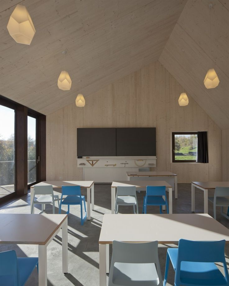 Steiner School / LOCALARCHITECTURE, classroom, wood ceiling and walls, teaching wall, pendant fixturesm concrete floors