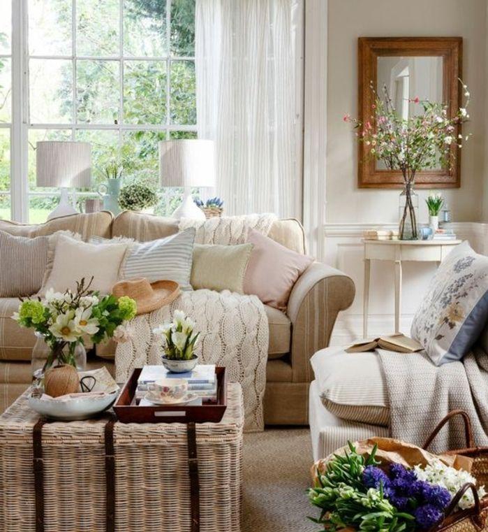 exemple deco campagne chic, table basse en rotin, canapéet fauteuil beige, coussins couleurs pastel, plaid et decoration fleurs
