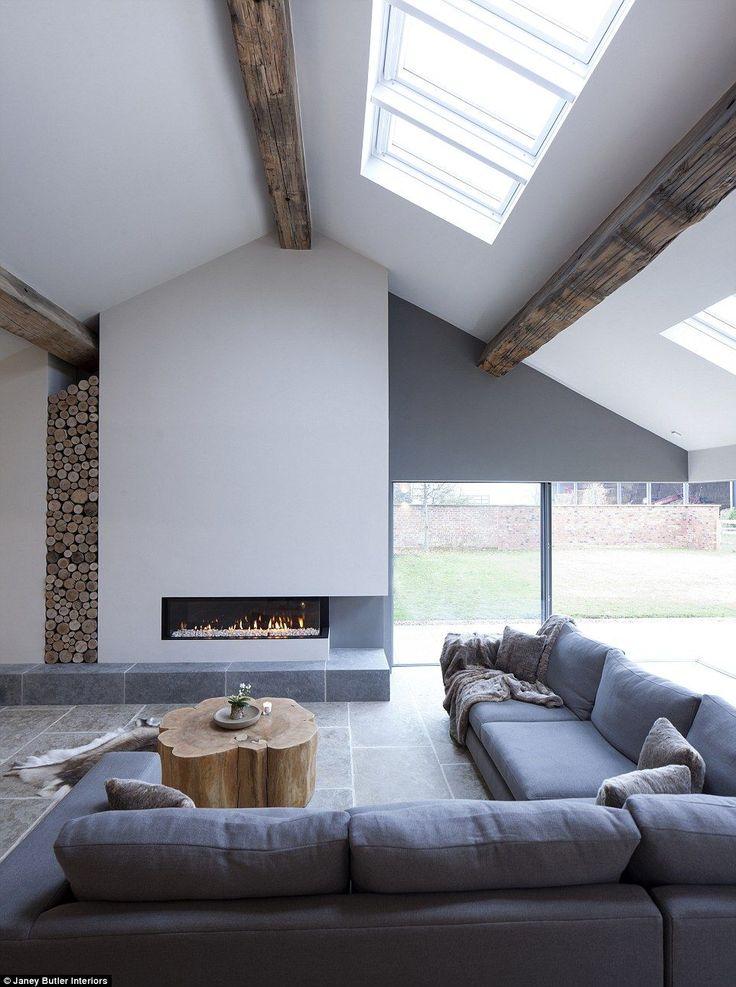 This Cheshire barn conversion designed by Janey Butler Interiors has a 'calming' colour scheme and features rustic tree trunk coffee tableand a floor-to-ceiling log stack for the fireplace