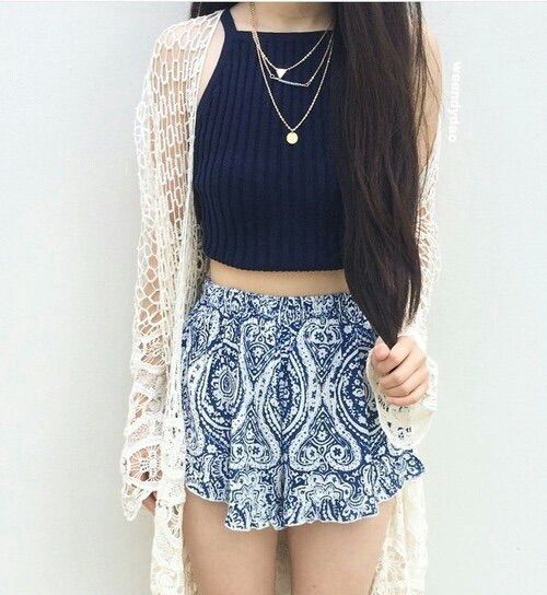 Crop top, shorts, cardigan and necklaces.