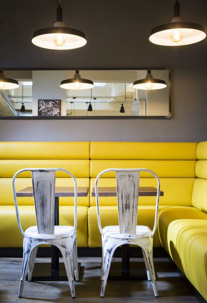 Yellow leather bench with industrial chairs.