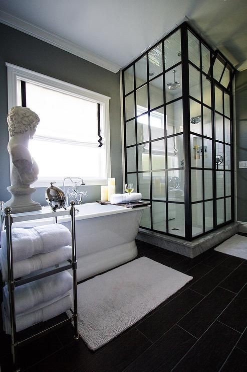 Gorgeous master bathroom boasts a freestanding oval tub and  a Pottery Barn Metal Etagere, placed under window dressed in a black and white roman shade, is situated next to a glass and steel shower enclosure clad in white subway tiles.