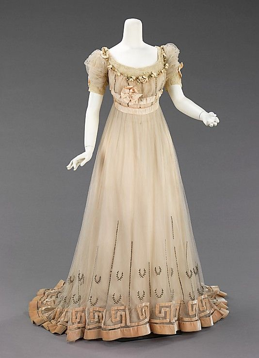 "Evening Dress, House of Paquin, French, 1905-07, silk, silver and rhinestones. ""Produced several years prior to the 1908 Hellenic designs of Paul Poiret, the raised waist and decorative references to Greek antiquity indicate this classical aesthetic and change of silhouette were in the air from 1905 on."""