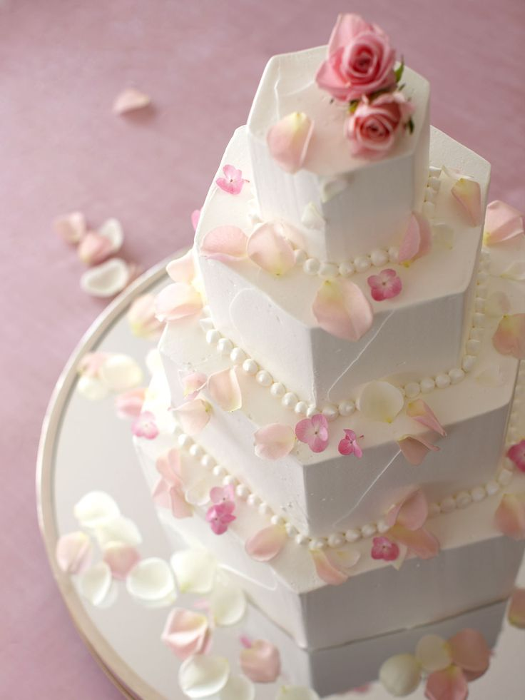 White layered wedding cake - hexagon shaped, with white pearls and pale pink flower petals