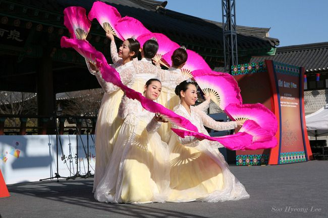 Buchaechum is a traditional form of Korean dance also called a fan dance, usually performed by groups of Korean female dancers.  Koreans use this dance during many celebrations. Dancers use large fans painted with pink peony blossoms and display a show of dance. In the dance being performed, the dancers represent shaped images using the fans e.g. birds, flowers, butterflies and waves.They wear b..