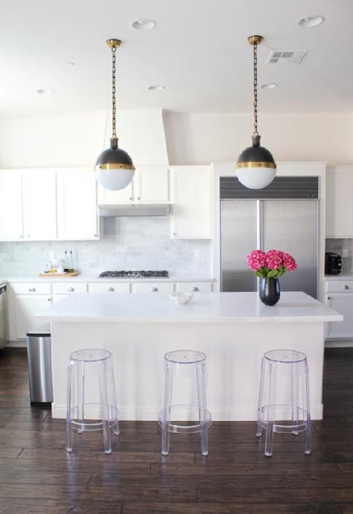 Gorgeous white gray blue kitchen deisgn with white kitchen cabinets, white carrara marble subway tiles backsplash, acrylic lucite modern stools and Thomas O'Brien Hicks pendants.