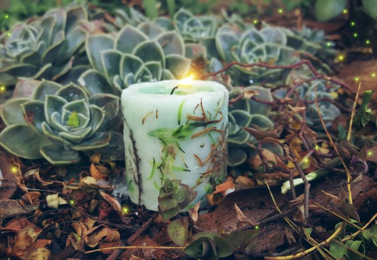 Green handmade candle  Decorated with flower and plant pieces. By White Feather Designs