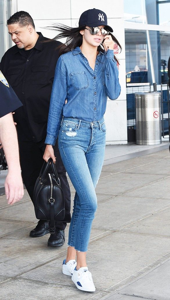 Kendall Jenner wears double denim with Puma sneakers, bowler bag, and baseball hat