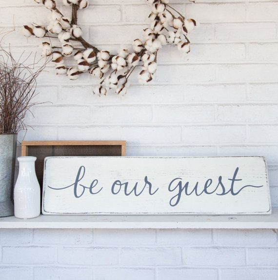 """Decorate your guestroom with this wooden """"be our guest"""" sign.  The lettering is hand painted and the background is a rustic, distressed, antique-white.  The size is 7.25"""" x 28"""".  Explore our Etsy shop to find other rustic wooden signs."""