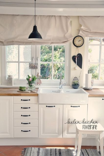 Not crazy about the curtains(?) But I love the windows over the sink.......why would you distract from their charm is strange