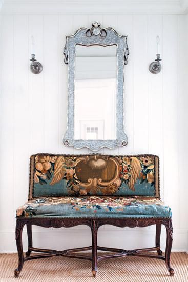 A settee with its original tapestry has a modern moment when paired with a Moroccan mirror and beadboard walls. | Connecticut Cottages & Gardens | January 2014