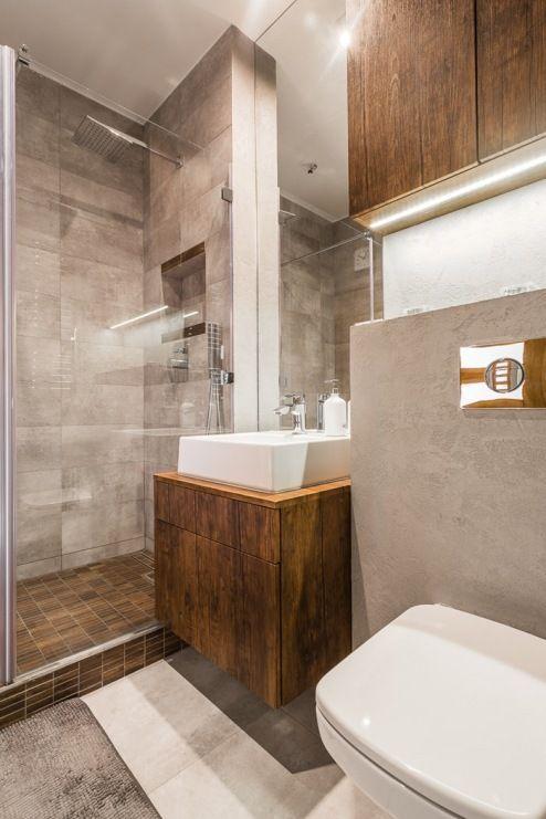 Nowoczesna łazienka w ciemnych kolorach, w której dużą rolę odgrywają tafle szkła. Podświetlenie oraz geometryczna...