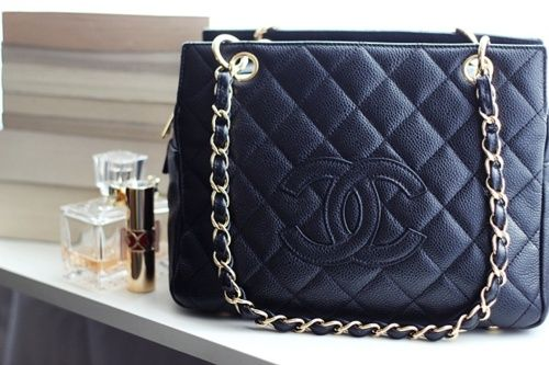 Chanel bag: navy, quilted pattern & silver chain interlaced with navy leather for short handles. Cute!