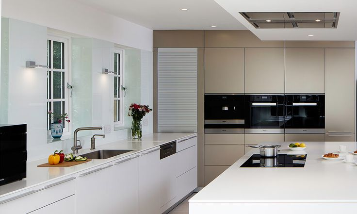 The shimmering sand beige aluminium tall units in this bulthaup b3 kitchen by hobsons choice blend perfectly with the kaolin laminate island and base units.