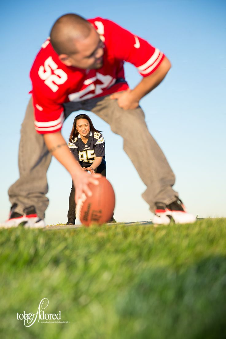 Engaged couple playing with a football in football jerseys