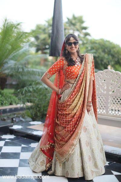 Sangeet Lehengas - Cream Lehenga with Orange Blouse | WedMeGood | Cream Lehenga with Orange Choli and Double Red Net Dupatta #wedmegood #indianbride #indianwedding #lehenga #bridal #cream #orange #choli #red