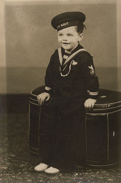 early 1900s black and white photo of a cute little boy in a U.S. Navy sailor outfit. ... can this little boy be any cuter?!? vintage childrens sailor suit and hat with spiffy white dress shoes. vintage, turn of the century, early 1900s, early 20th century, antique photography.