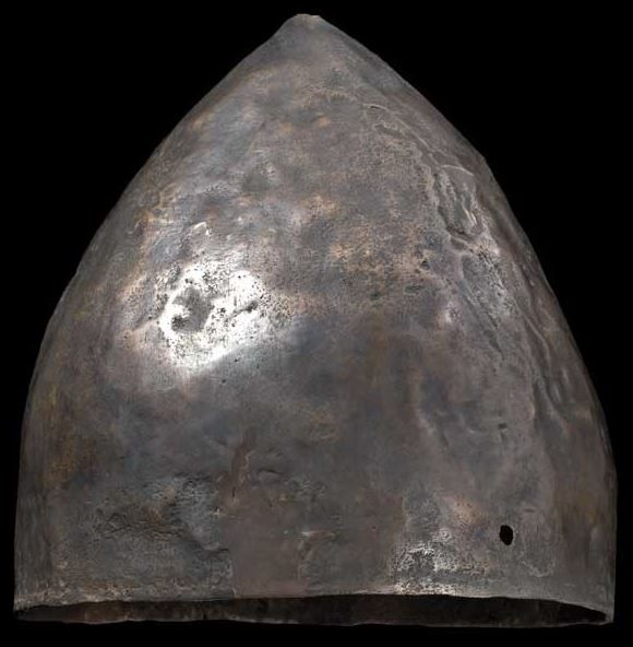 Near Eastern helmet, 1st half of the 1st millennium B.C. A conical helmet of bronze (large percentage of copper), the small button-shaped top knob missing. Two holes on the edge at the sides for attaching the chin straps, 20 cm high. Private collection, from Hermann Historica auction