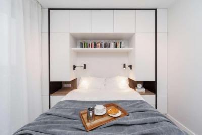 Biała sypialnia z kontrastowymi czarnymi elementami.  White bedroom with black elements.