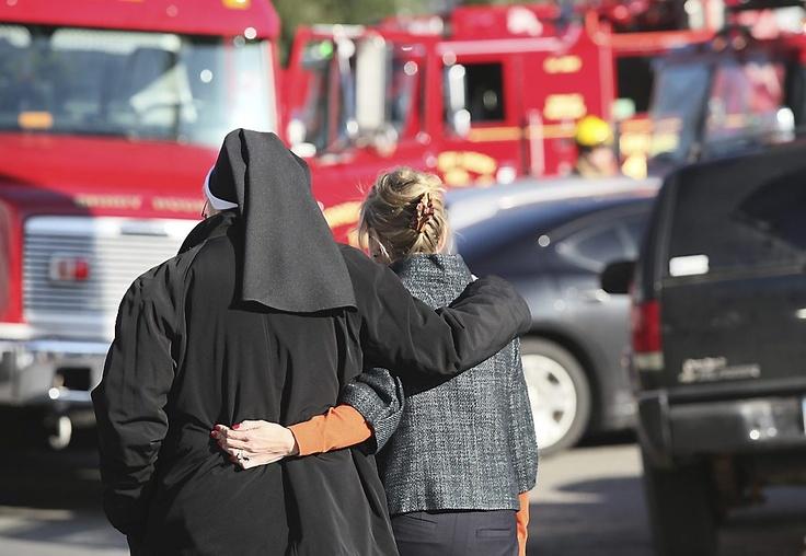 Een non ontfermt zich over een van de leerlingen van de school in Newtown. Twintig kinderen, zeven volwassenen en de schutter vonden de dood bij een bloedige schietpartij.  Foto EPA