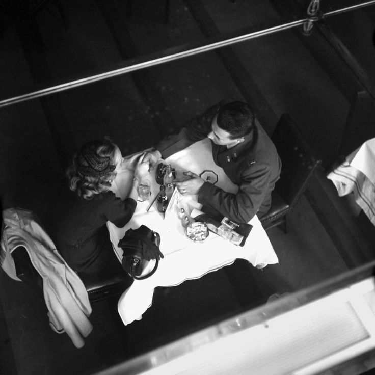 A couple having a meal at a scenic restaurant seen from above. End of April, 1953, New York, NY