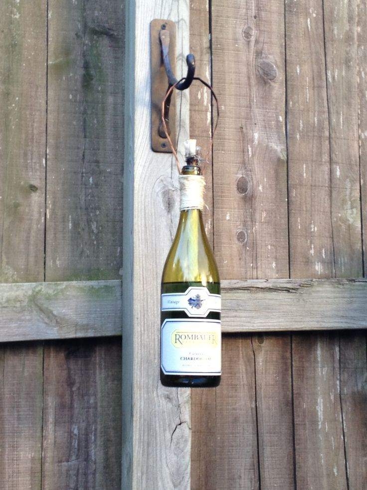 wine bottle torch on fence | Wine bottle tiki torches mounted on the fence!