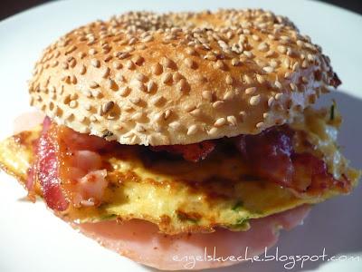 Frühstücks-Bagel mit Frischkäse, Rührei, Schinken und Speck