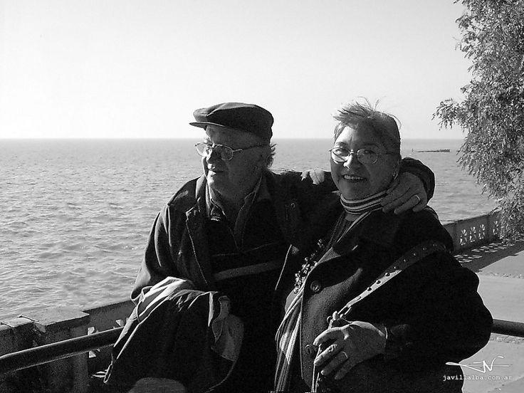 Una pareja de abuelos saborea el sol rioplatense paseando por la Costanera de Buenos Aires, En una mañana de otoño presumen de un matrimonio en eterna primavera.