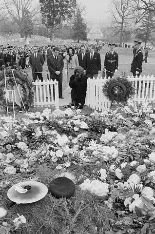 Jacqueline Kennedy stands in front of her husband's grave at Arlington National Cemetery on November 28, 1963. With Mrs. Kennedy are, John J. McNally, Jr., Larry O'Brien, Pierre Salinger and Kenneth O'Donnell, all of the White House staff, and her sister, Princess Lee Radziwill. Mrs. Kennedy kneels and makes the sign of the cross. The eternal flame she lit on the day of the funeral is seen in the foreground.